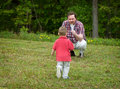 Come make a wish father holding dandelion while his son young boy walks towards him focus is on the boy Royalty Free Stock Images