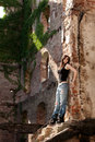 Come and save me beautiful woman with trendy style in torn jeans leaning to a brick wall Royalty Free Stock Photography