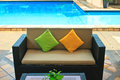 Comfortable sofa near swimming pool in the garden Royalty Free Stock Photos