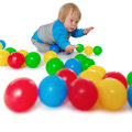 Comical child playing with colored plastic balls on white floor Stock Photo