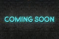 `COMING SOON` neon sign shining on black brick wall,Business concept