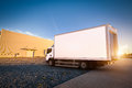 Commercial delivery truck with blank white trailer on cargo parking.