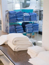 Commercial hospital laundry a variety of towels and uniforms neatly folded in a facility Stock Photos