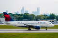 Commercial jet on an airport runway with city skyline in the bac charlotte background Royalty Free Stock Photo