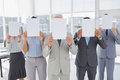 image photo : Buisness team holding up blank pages and covering their faces