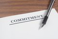 Commitment letter and pen at wooden board Royalty Free Stock Photo