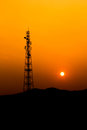 Communication antenna tower telecommunications with sunset sky silhouette Stock Images
