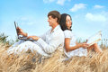 Communication beautiful couple sitting on grass with laptop and book against sky background Stock Photos