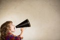 Communication concept kid shouting through vintage megaphone Stock Photos