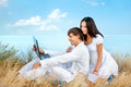 Communication happy young couple with laptop against sky background Stock Photos