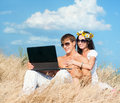 Communication happy young couple in sunglasses with laptop against sky background Stock Image