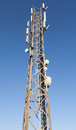 Communication radio tower with devices above blue sky Royalty Free Stock Images