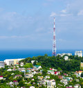 Communication tower in the city by sea Royalty Free Stock Images
