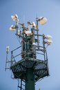 Communication tower with multiple antennas and blue sky in background Stock Photo