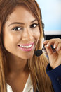 Communication woman talking on a headset in business suit looking at camera smiling Stock Photography
