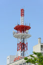 Communications tower with antennas against blue sky Stock Photos