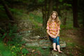 Communing with nature pretty girl sitting out on a rock in a forest during the summer Stock Photo