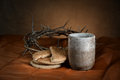Communion cup and bread with crown of thorns in background Stock Photos