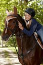 Communion between rider and horse female caressing while riding in the woods Royalty Free Stock Photography