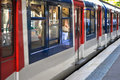 Commuter train at station platform red white blue Stock Photos