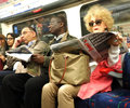 Commuters in london underground sit and some read papers during the rush our uk Royalty Free Stock Photos