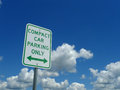 Compact Car Parking Only Sign with blue sky and clouds Royalty Free Stock Photo