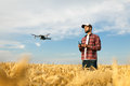 Compact drone hovers in front of farmer with remote controller in his hands. Quadcopter flies near pilot. Agronomist Royalty Free Stock Photo