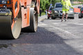 Compactor on hot asphalt at renewal project local street with traffic in background Royalty Free Stock Photos