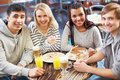 Company of friends image teenage enjoying themselves in cafe Royalty Free Stock Images