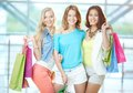 Company of shoppers portrait three happy girls in smart casual holding paperbags Royalty Free Stock Photography