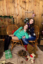 Company of two girls with gifts in the room with wooden walls and christmas and christmas decor new year conception Stock Photo