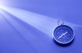 Compass in a beam of light conceptual image magnetic used for navigation and direction finding on blue surface with Royalty Free Stock Images