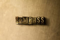 COMPASS - close-up of grungy vintage typeset word on metal backdrop