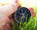 Compass in hand on a background of green grass Royalty Free Stock Images