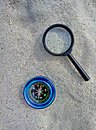 Compass and magnifier on sand
