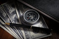 Compass and pen on money with book. Royalty Free Stock Photo