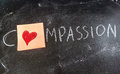 Compassion concept on chalk table whit a red heart Royalty Free Stock Photography