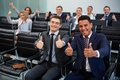 Competency two happy young businessmen showing thumbs up on background of their colleagues Royalty Free Stock Photos