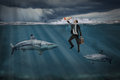 Competitive business concept busines with businessman swiming among sharks in stormy seas Stock Photo