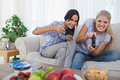 Competitive friends playing video games and having fun at home on the couch Stock Photos