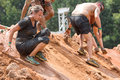 Competitors Slide Down Slippery Hill At Extreme Obstacle Course Race