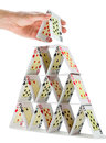 Completing a house of cards isolated on white Royalty Free Stock Photo