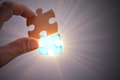 Completing the last piece of jigsaw puzzle light glow from empty space Royalty Free Stock Photography