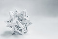 Complex tetraeder folded paper origami on a white background