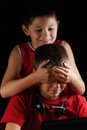 Complicate playing boy covers brother s eyes while computer game Royalty Free Stock Photos
