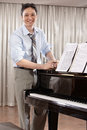 Composer a young music standing near grand piano Royalty Free Stock Photography