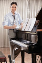 Composer a young music standing near grand piano Stock Images