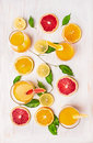 Composing of citrus juices and a slice of orange grapefruit and lemon with green leaves on white wooden background top view Royalty Free Stock Photos
