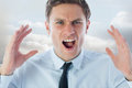 Composite image of angry businessman shouting against clouds in a room Stock Photo
