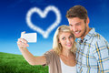 Composite image of attractive couple taking a selfie together Royalty Free Stock Photo